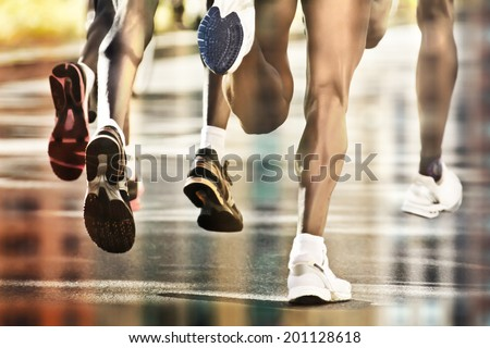 Runners on wet ground with city reflection - stock photo
