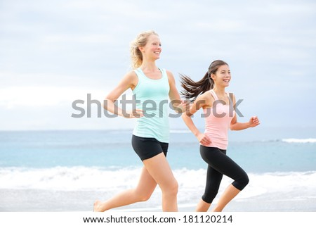 Runners - two women running outdoors training. Exercising female athletes jogging outside on beach smiling happy. Multiracial Asian and Caucasian woman in healthy lifestyle. - stock photo