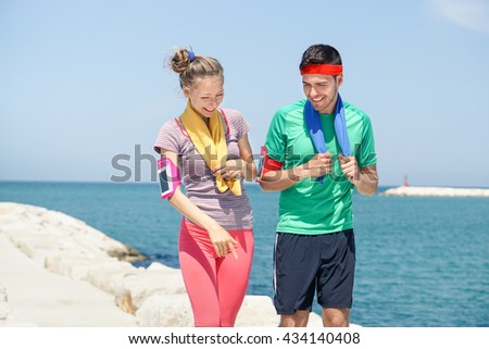 Runners walking after training next beach jogging route - Young cheerful couple having fun together outdoor - Sport and healthy lifestyle concept - Soft focus on man with warm filter - stock photo
