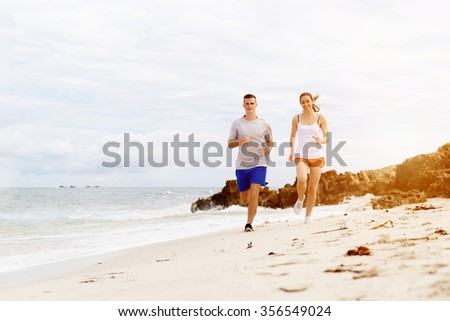 Runners. Young couple running on beach together - stock photo