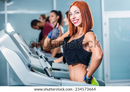 Running and health. Sport and slender girl running on a treadmill and smiling at the camera. Athlete dressed in sports uniforms and running in the gym showing thumb up. - stock photo