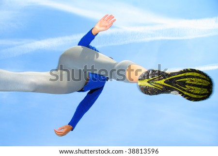 Running and jumping over the camera. Speed and action composition. Shallow depth of field, focus on the female running shoe. - stock photo