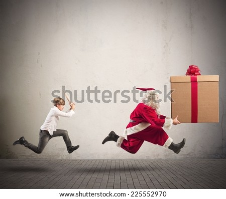 Running angry child chasing Santa Claus with a big present - stock photo