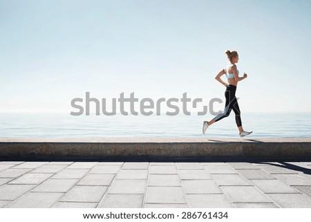 Running asian woman. Female runner training outdoors seaside athlete on beautiful sunset or morning at beach. - stock photo