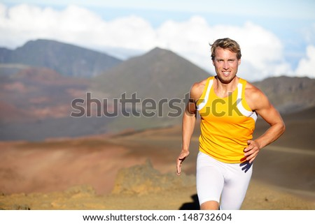 Running athlete - man runner sprinting fast. Male sport fitness model training a sprint in amazing nature landscape outdoors at speed wearing sporty runners compression clothes shorts. Strong fit man - stock photo