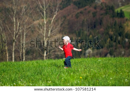 Running baby at mountains background in summer