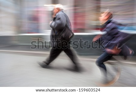 Running boy and an elderly man walking along the streets of the old town. Intentional motion blur - stock photo