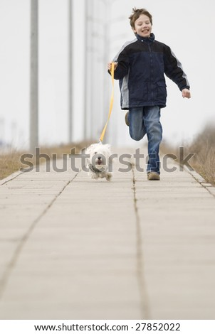 Running boy with his dog - stock photo