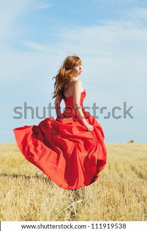 Running bride in red wedding dress in a field with haystack - stock photo