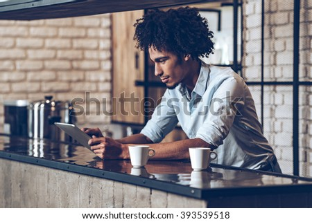 Running business easier with technologies. Side view of young African man using his digital tablet while leaning at bar counter with two coffee cups - stock photo
