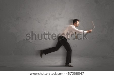 Running businessman in a rush with device in hand on background