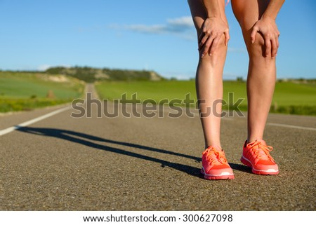 Running challenge concept. Runner legs and sport shoes on asphalt countryside road ready for training. - stock photo