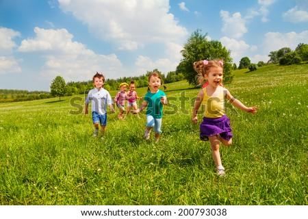 Running children in green field during summer - stock photo