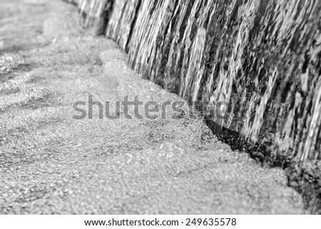 Running clean water with sparkling drops, detailed black and white image - stock photo