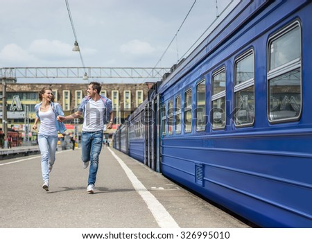 Running couple at the train station - stock photo