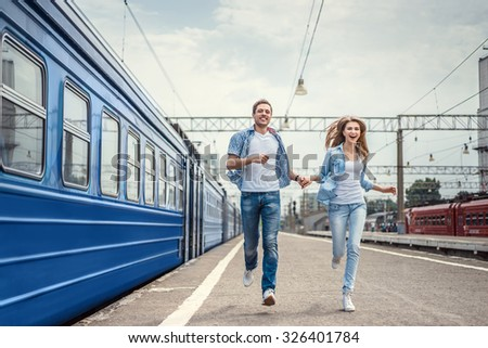 Running couple in a train station - stock photo
