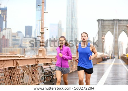 Running couple. Runners jogging outside in rain. Asian woman and Caucasian man runner and fitness sport models training outdoor on Brooklyn Bridge, New York City, USA. - stock photo