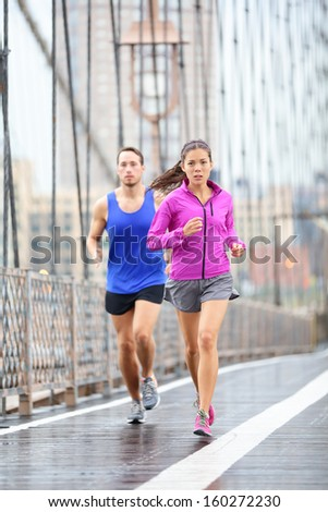Running couple. Runners jogging outside in rain. Woman and man runner athletes training outdoor for marathon on Brooklyn Bridge, New York City, USA. Asian female and Caucasian male fitness sport model - stock photo