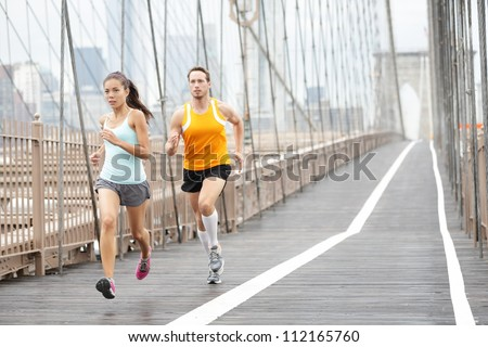 Running couple. Runners training outside. Asian woman and Caucasian man runner and fitness sport models jogging in full body showing Brooklyn Bridge, New York City, USA. - stock photo