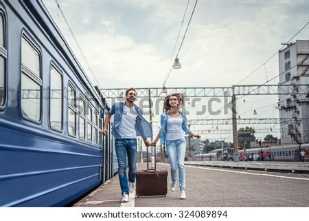 Running couple with a suitcase in a train station - stock photo