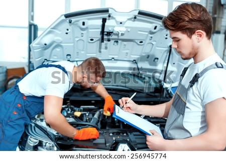 Running diagnostics. Two handsome car mechanics in uniform checking the engine under hood in the car service station and checking in service order - stock photo