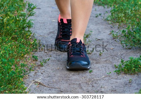 Running fitness concept. Close-up view of walking or running woman shoes in use on road in the park