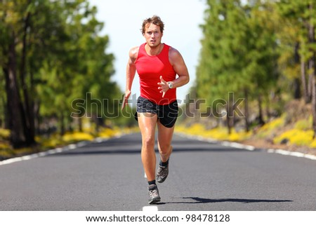 Running fitness sport man. Male runner sprinting on road - fit muscular male model training for marathon running fast on beautiful road in nature. - stock photo