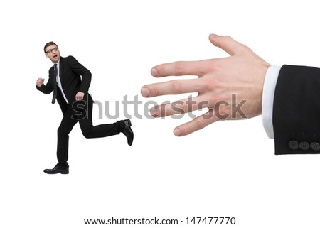 Running from big hand. Terrified young businessman running from a big human hand while isolated on white - stock photo
