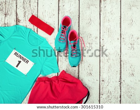Running gear laid out ready for a race day, rustic wooden background with copy space - stock photo