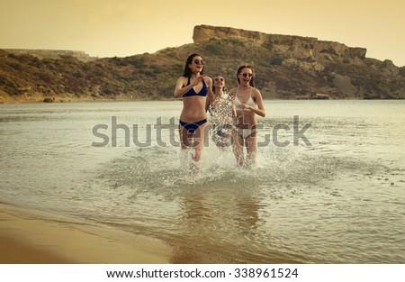 Running girls at the beach - stock photo