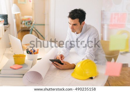 running home office. running his business from home man working on tablet in office