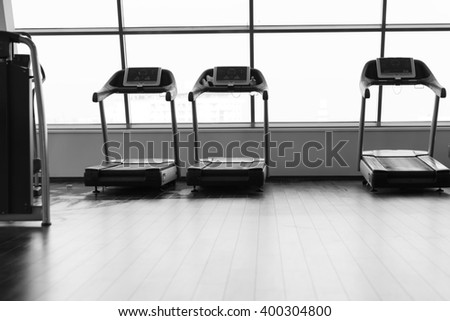 running in a gym on a treadmill concept for exercising, fitness and healthy lifestyle - stock photo