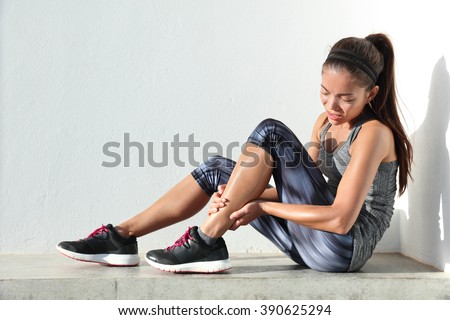 Running injury leg accident- sport woman runner hurting holding painful sprained ankle in pain. Female athlete with joint or muscle soreness and problem feeling ache in her lower body. - stock photo