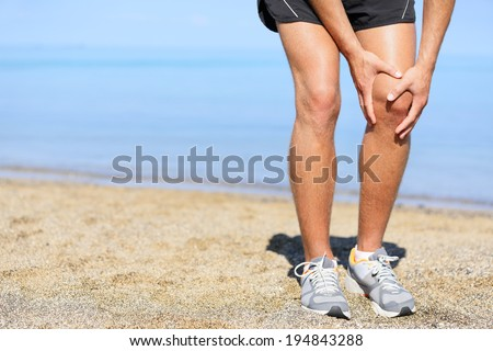Running injury - Man jogging with knee pain. Close-up view of runner injured jogging on the beach clutching his knee in pain. Male fitness athlete. - stock photo