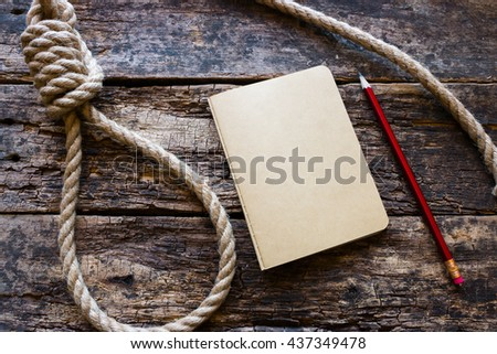 running knot and a suicide note on a wooden background - stock photo