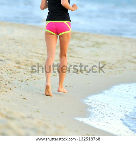 Running legs and shoes of runner jogging on beach - stock photo