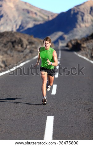Running. Male athlete running training for marathon on beautiful mountain road. Man fitness sports model sprinting fast. - stock photo