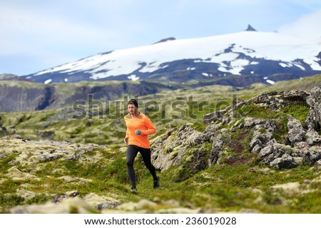 Running man athlete exercising trail runner. Fit male sport fitness model training and jogging outdoors in beautiful mountain nature landscape by Snaefellsjokull, Snaefellsnes, Iceland. - stock photo