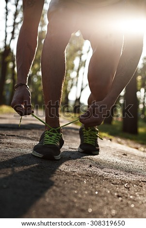 Running man closeup of running shoes on sunset or sunrise. Runner feet. Male sport fitness runner tying the laces of his shoes. Man fitness jog workout wellness on forest background. - stock photo