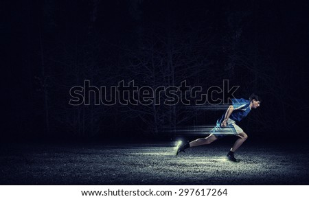 Running man in blue sport wear on black background - stock photo