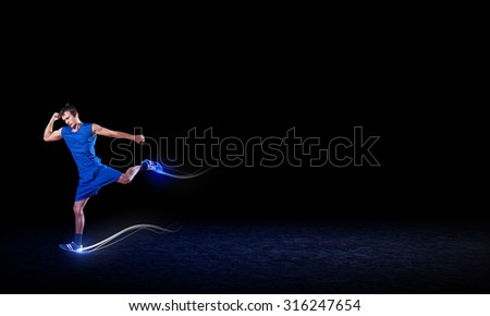 Running man in blue sport wear on black background