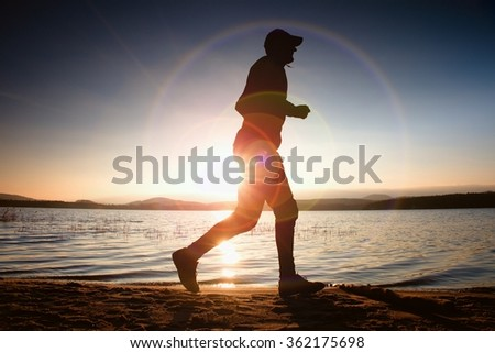 Running man in Sun rays on beach. Sportsman in baseball cap, jogging during the sunrise above sea level. Strong flare effect.