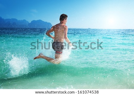 running man in water of tropical sea