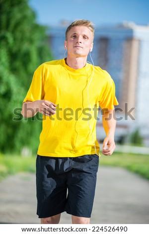 Running man jogging in city street park at beautiful summer day. Sport fitness model caucasian ethnicity training outdoor. Jogger listening training music on smartphone  - stock photo