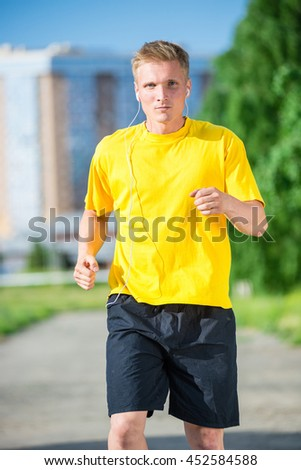 Running man jogging in city street park at beautiful summer day. Sport fitness model caucasian ethnicity training outdoor. Jogger listening training music on smartphone  - stock photo