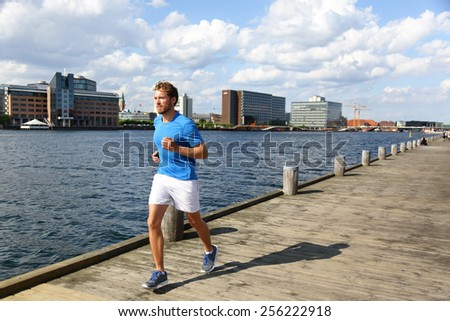 Running man jogging in modern city. Male runner exercising on Copenhagen boardwalk in Bryggen, Denmark. - stock photo