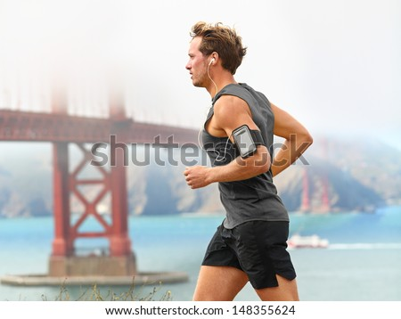 Running man - male runner in San Francisco listening to music on smart phone. Sporty fit young man jogging by San Francisco Bay and Golden Gate Bridge. Jogger listening to training music on smartphone - stock photo