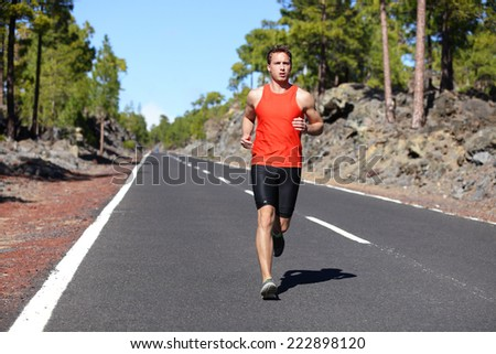 Running man - male runner jogging outdoors on road training for marathon run as part of healthy lifestyle. Close up of fit fitness model during outdoor workout in summer. Caucasian guy. - stock photo