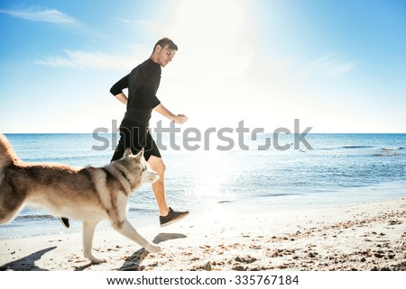 Running man. Male runner jogging with siberian husky dogs during the sunrise on beach - stock photo