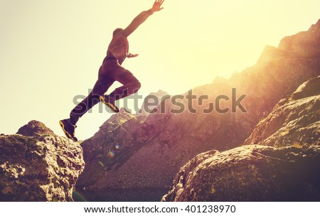 Running Man on Mountains jumping cliff over lake Skyrunning sport Lifestyle Travel concept outdoor  - stock photo